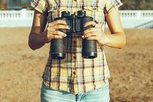An unrecognizable young girl in a yellow shirt is standing on the shore holding binoculars
