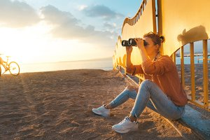 Young beautiful girl traveler sits on a sandy beach at sunset and looks through binoculars