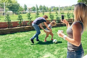Mother taking photo of her husband and son playing