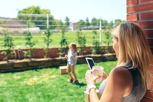 Mother watching mobile while son plays