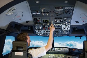 Rear view of young male pilot switching controls in air vehicle