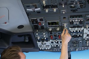 Rear view of male pilot switching controls in air vehicle