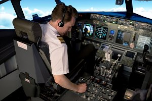 High angle view of young male pilot switching control while sitting in cockpit