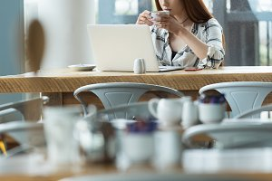 Woman having coffee while using laptop computer