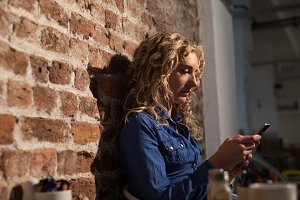 Side view of woman using phone while sitting by brick wall