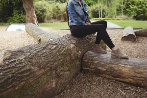 Low section of woman sitting on fallen tree