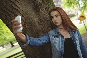 Woman taking selfie while standing by tree