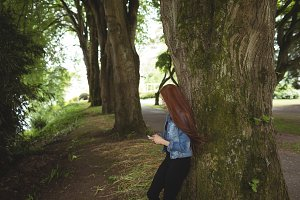 Side view of woman using phone while leaning on tree