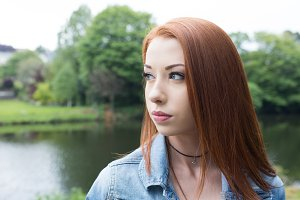 Thoughtful woman looking away while standing against lake