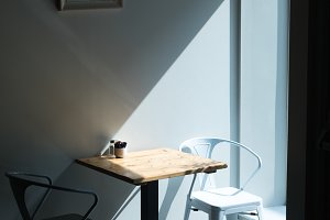 Empty chair at table by wall