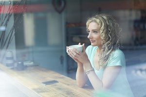 Smiling woman looking away while sitting in cafe