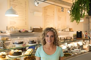 Portrait of smiling woman standing in cafe