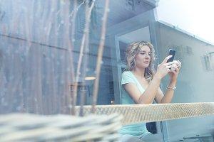 Woman using phone seen through glass