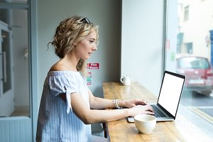 Side view of woman using laptop while sitting by window