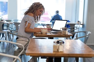 Side view of young woman writing while using laptop at table