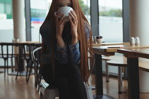 Portrait of young woman having coffee in cafe