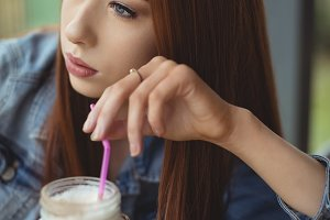 High angle view of thoughtful woman having drink in cafe