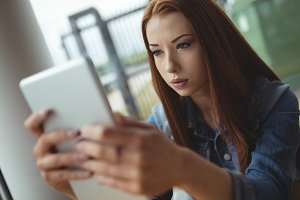 Close up of young woman using digital tablet