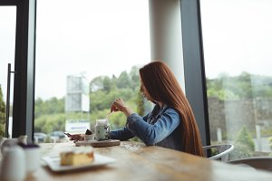 Side view of woman having drink while sitting at cafe