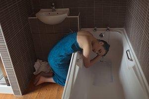 Full length of woman washing hair in bathtub at bathroom