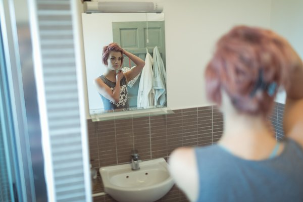 Reflecting of woman on mirror in ba…