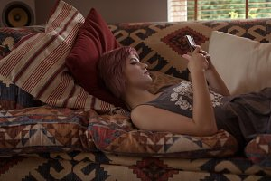 Woman using phone while relaxing on sofa