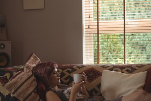 Side view of woman having coffee on sofa