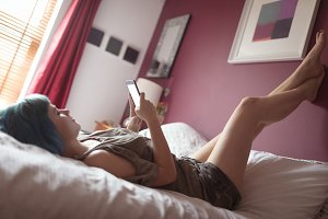 Woman using phone on bed with feet up