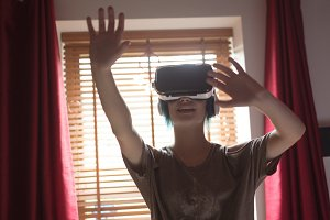 Woman gesturing while using virtual reality headset