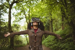 Woman with arms outstretched wearing virtual reality simulator
