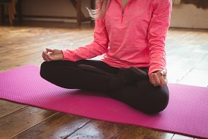 Low section of young woman meditating on exercise mat