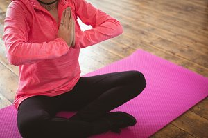 Low section of woman meditating on exercise mat