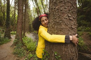 Woman hugging tree at forest