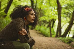 Thoughtful woman looking away at forest