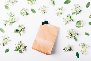 Paper gift bag and green flowers