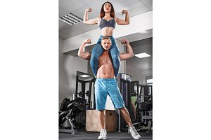 sport fit couple at gym. work in pairs with dumbbells