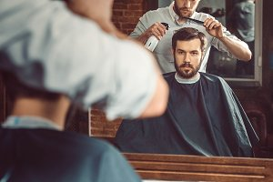 Young handsome barber making haircut of attractive man in barbershop