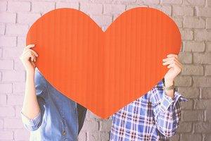 Couple holding handmade paper heart