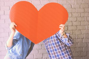 Couple holding handmade paper heart