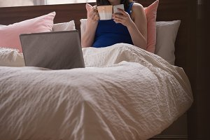 Relaxed woman having coffee while using phone on bed