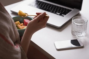 Cropped hand of woman having fruit by laptop
