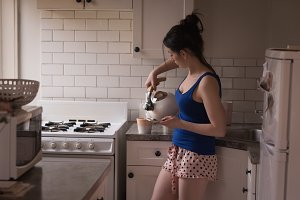 Woman pouring coffee from kettle in cup at kitchen