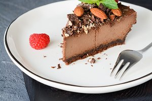 Slice of chocolate cheesecake with raspberries, nuts and mint