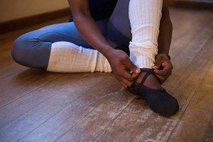 Ballerino tying his ballet shoes in the studio