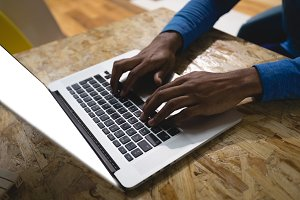 Cropped hands of man using laptop in cafe