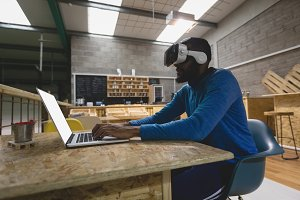 Man using laptop while looking through virtual reality in cafeteria