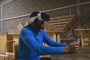 Man using mobile phone while looking through virtual reality