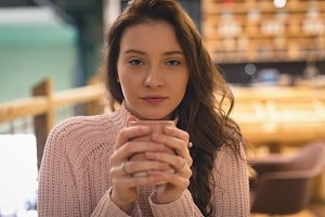 Beautiful woman having cup of coffee in café