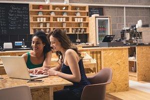 Female friends using laptop in café