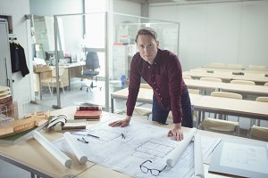 Portrait of confident architect standing at table